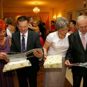 Fotoksiążka, zdjęcie rodziców na ślubie oglądających fotoalbum