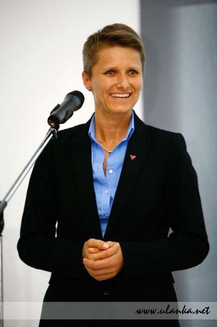 Fotografia reportażowa, uśmiechnięta kobieta przed mikrofonem