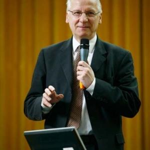 Fotografia reportażowa, mężczyzna w garniturze przemawia na konferencji
