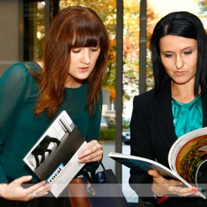 Fotografia reportażowa, dwie kobiety przeglądające katalogi na konferencji
