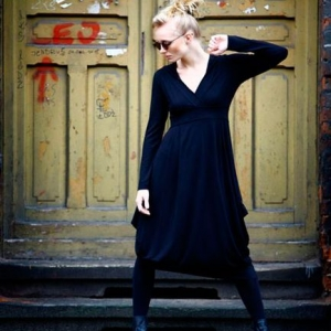 Fotografia modelki w czarnej sukni na tle starych drewnianych drzwi