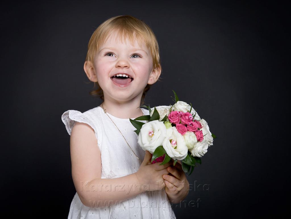 uśmiechnięta dziewczynka z kwiatami