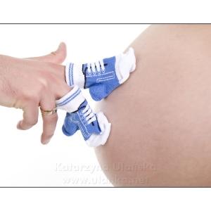 Fotografia ciążowa, małe niebieskie buciki na brzuszku kobiety w ciąży