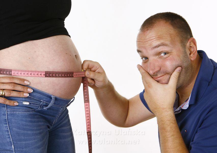 Fotografia ciążowa, mężczyzna mierzący obwód brzucha żony w ciąży
