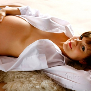 Fotografia ciążowa, kobieta w ciąży leżąca na łóżku w białej koszuli