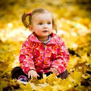 Dziewczynka bawiąca się w liściach