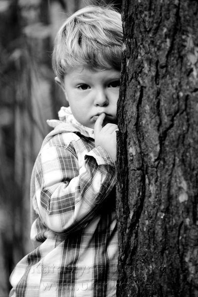 Fotografia chłopca za drzewem