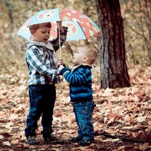 Dwaj chłopcy pod parasolką wśród liści