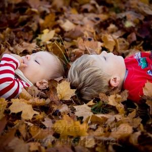 Dzieci leżące wśród liści