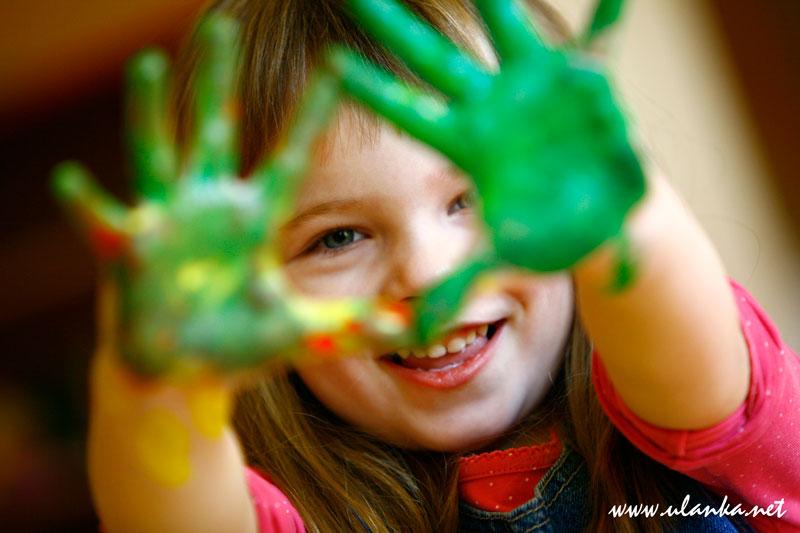 Fotografia dziecięca - uśmiechnięta dziewczynka z pomalowanymi rękoma na zielono