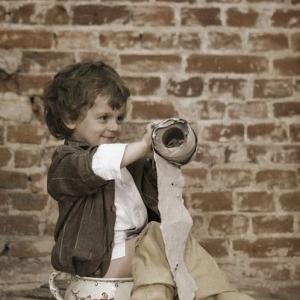 Mały chłopiec na tle muru
