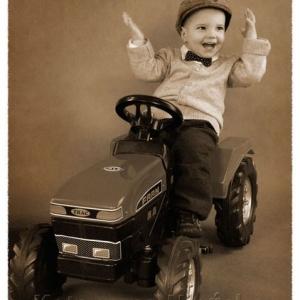 Fotografia chłopca na traktorze zabawce