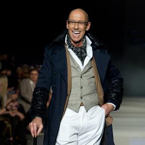 Fotografia eventowa, pokaz mody, uśmiechnięty model w eleganckim stroju z laską