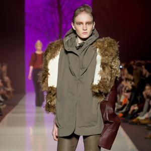 Fotografia eventowa, pokaz mody, modelka w beżowym stroju w broązowych kozakach
