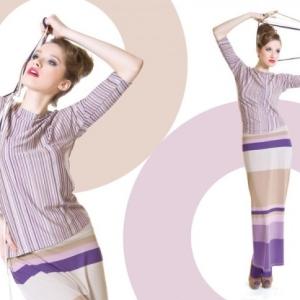 Modelka w beżowym swetrze i spódnicy w paski