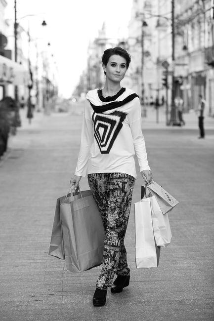 Fotografia mody, czarno białe zdjęcie pięknej modelki idącej z zakupami