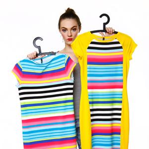 Moda, modelka trzymająca wieszaki z kolorowymi strojami