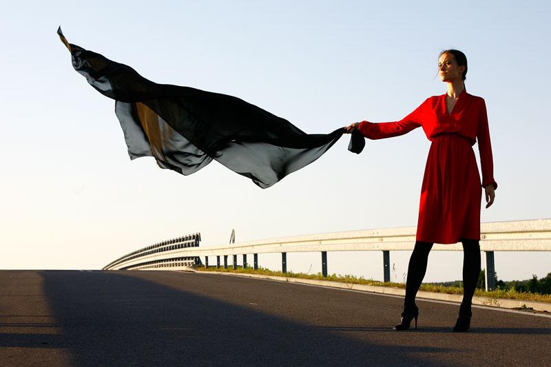 Fotografia mody, modelka w czerwonej sukni stojąca na jezdni