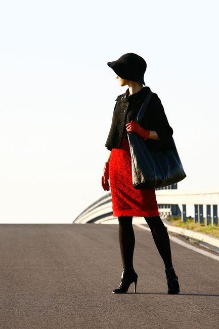 Fotografia mody, modelka na ulicy w czerwonej sukience i czarnym żakiecie i kapeluszu