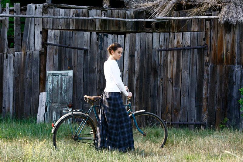 Fotografia mody, modelka przy rowerze na tle stodoły
