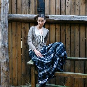 Moda, modelka w sukience w kratę siedząca w stodole