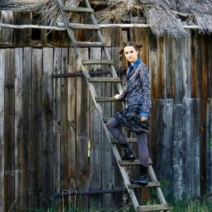 Modelka stojąca na drabinie przy stodole