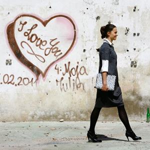 Fotografia mody, modelka z aktówką na tle starego muru