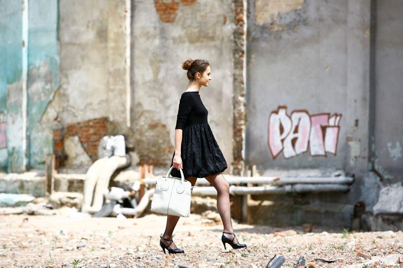 Fotografia mody, idąca modelka w czarnej sukience na tle starego muru