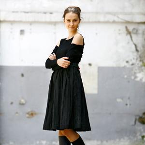 Fotografia mody, modelka w czarnym stroju na tle szarego muru