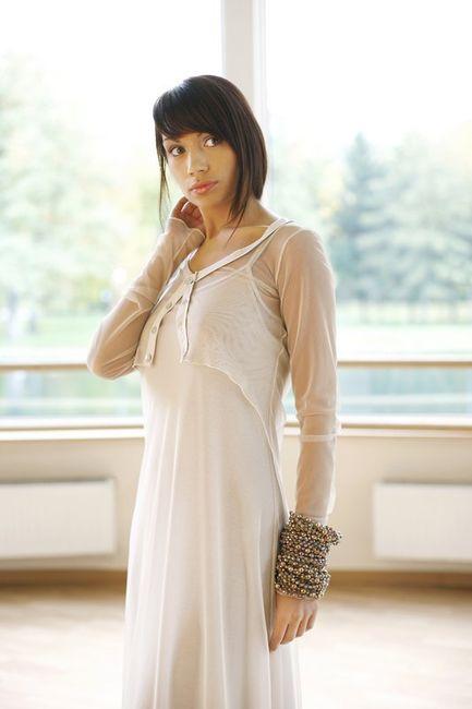 Fotografia mody, modelka w jasnym stroju na tle okna