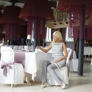 Fotografia mody, modelka siedząca przy stoliku na pustej sali restauracyjnej