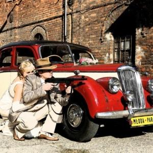 Fotografia ślubna - sesja plenerowa stylizowana na lata 40 gangsterskie - para młoda za samochodem z karabinem