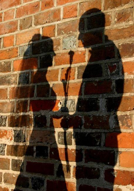 Zdjęcia ślubne w plenerze - xień małżonków na ścianie z cegły