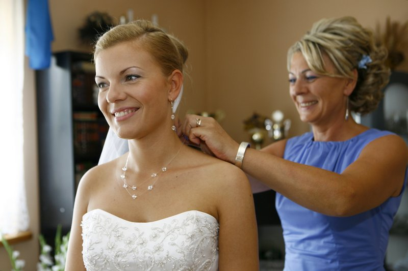 Fotografia ślubna - przygotowania, matka przypina welon córce