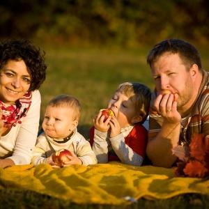 Fotografia rodzinna leżąca w parku na kocu