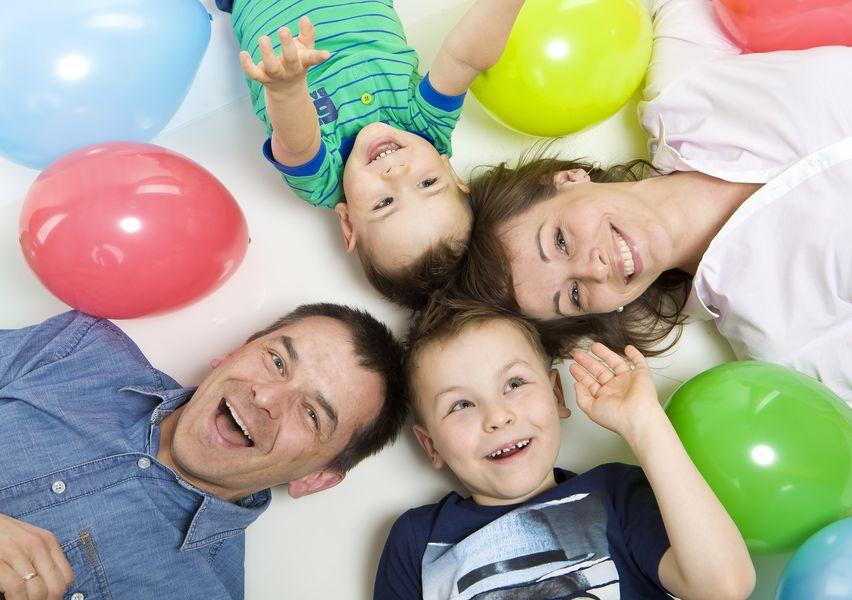 Fotografia rodzinna, zdjęcie rodziny leżącej na ziemi wśród balonów, ujęcie z góry