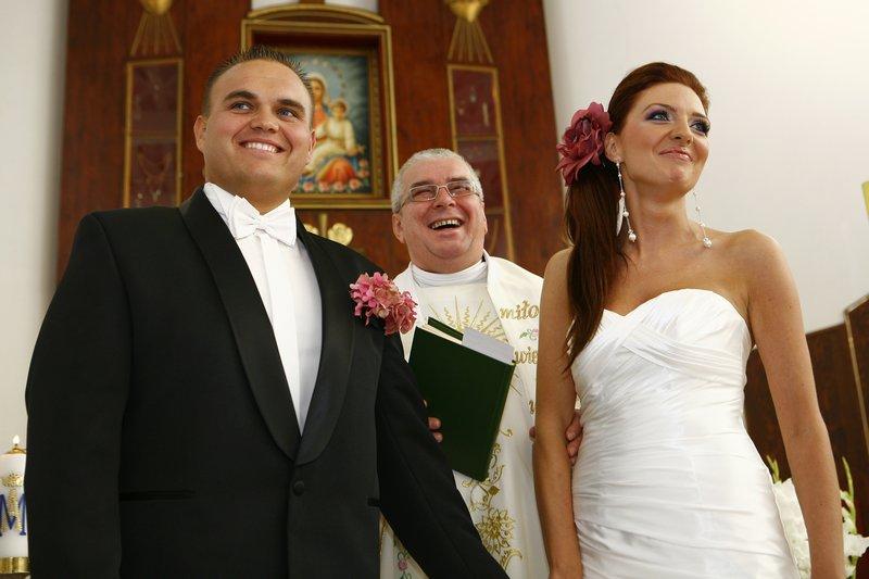 Fotografia ślubna, para młoda w kościele z księdzem