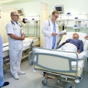 fotografia wizerunkowa kliniki, lekarze stojący przy łóżku pacjenta