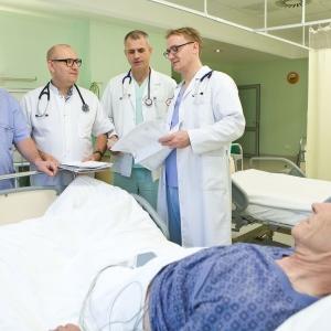 fotografia wizerunkowa kliniki, lekarze stojący przy łóżku starszego pacjenta