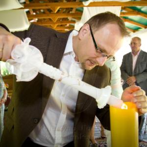 Ojciec chrzestny zapala świecę
