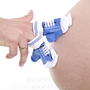 Zdjęcie brzucha kobiety w ciąży i małe skarpetki