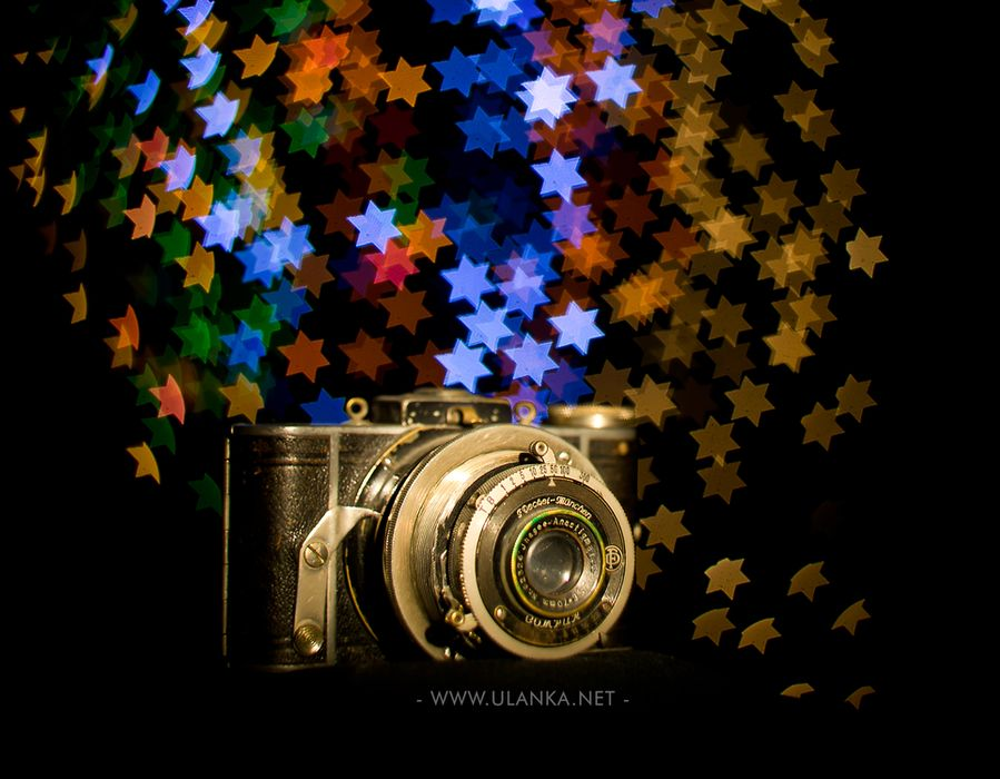 Efekt bokeh, stary aparat fotograficzny na tle efektu bokeh gwiazdki
