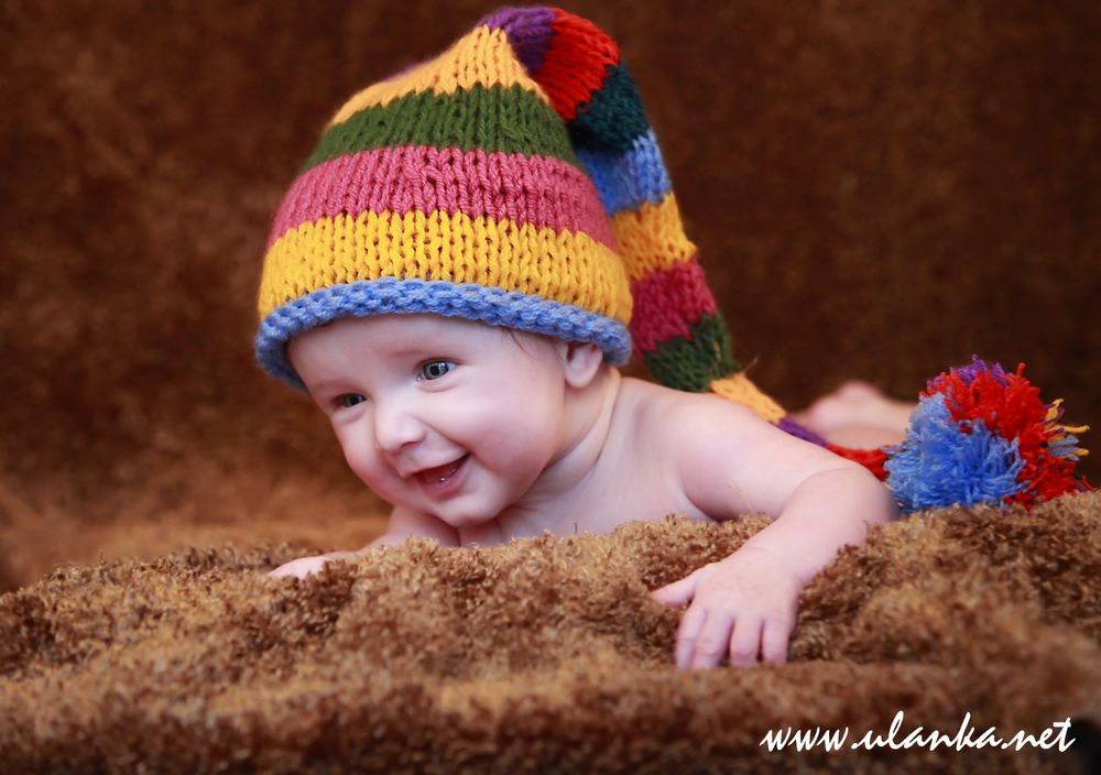 Zdjęcia noworodków i niemowlaków, uśmiechnięte dziecko w kolorowej czapce