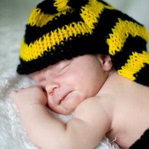 Śpiący malec w czarno żółtej czapce