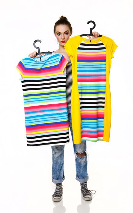 Kobieta trzymająca wieszaki z kolorowymi ubraniami